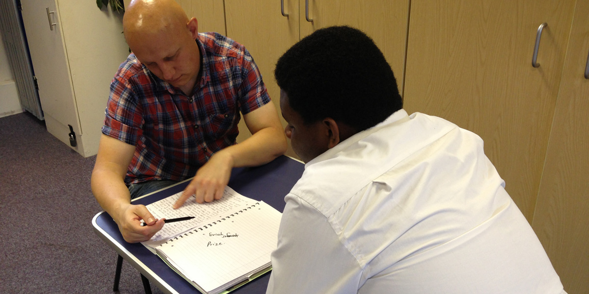 A mentor looks through a student's writings